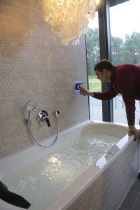 In der Badausstellung zeigt ein Fachmann einen Whirlpool für ein Komfortbad.